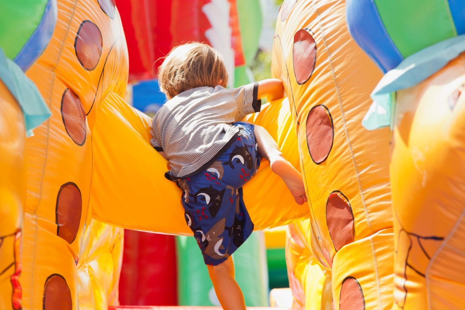 Boy playing in bouncy castle, rear view